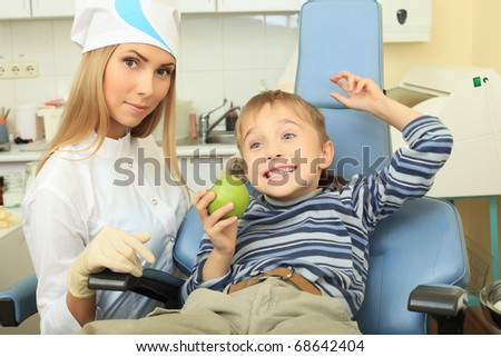 Shot of a smiling little boy with dentist in a dental surgery. Healthcare, medicine. - stock photo