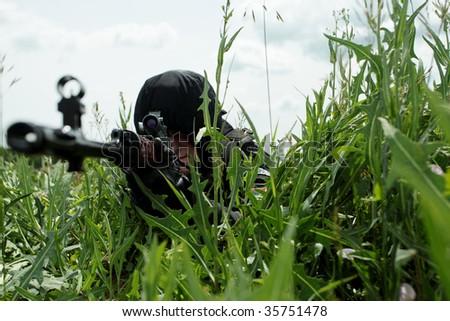 Shot of a soldier holding gun at a battlefield. - stock photo