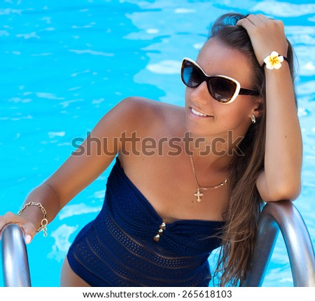 Shot of a teen girl enjoying a day at the luxury poolside, tanning. Girl at travel spa resort pool. Summer luxury vacation.  - stock photo