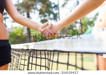Shot of a two young tennis players shaking hands over the net - stock photo