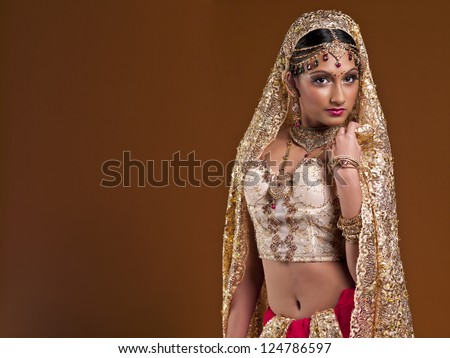 Shot of a woman in a traditional garb, on a spice colored background. - stock photo