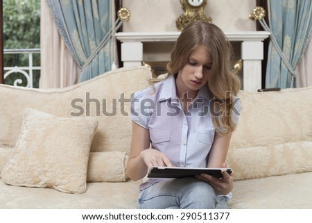 Shot of a woman relaxing on a sofa with her digital table - stock photo
