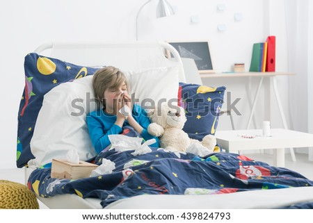 Shot of a young boy laying in a bed and blowing his nose - stock photo