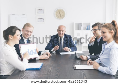 Shot of a young elegant businesswoman showing the results during business conference - stock photo