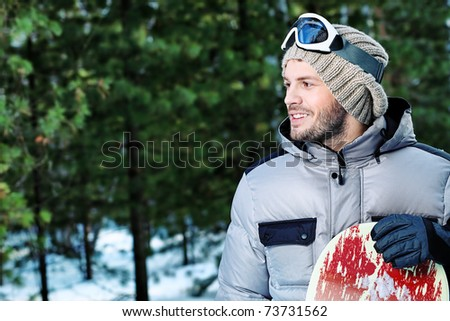 Shot of a young man with a snowboard outdoor. - stock photo