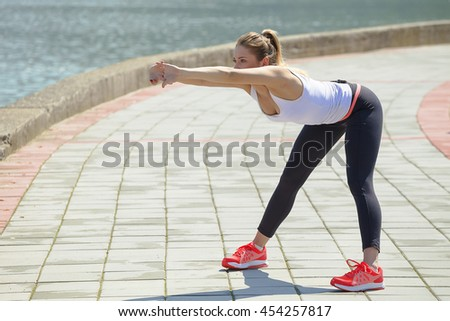 Shot of a young women stretching by the water - stock photo