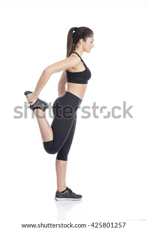 Shot of a young women stretching her leg. Studio shot, Isolated on white. - stock photo