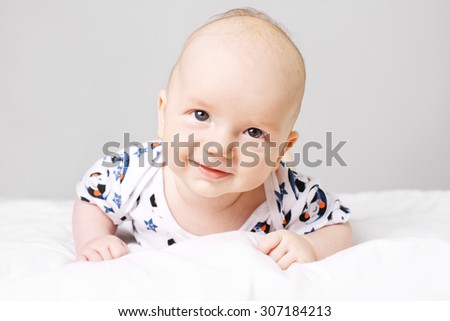 Shot of an adorable, little caucasian boy laying on bed and smiling. He is looking straight into camera. - stock photo