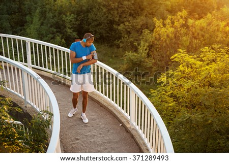 Shot of an attractive and sporty young man starting his music playlist. - stock photo