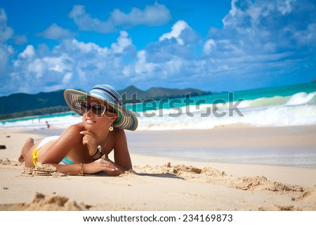 Shot of an attractive young sexy woman in a bikini relaxing at the beach. Beautiful beach holiday in Hawaii - stock photo