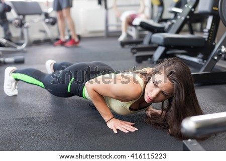 Shot of an attractive young woman working out at the gym - stock photo