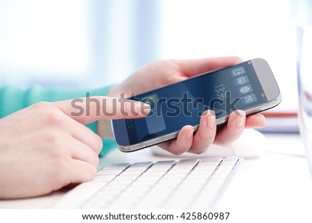 Shot of an businesswoman using her mobile phone while sitting at office in front of computer. - stock photo