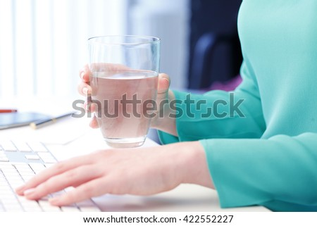 Shot of an professional woman holding in her hand a glass of water while sitting at office in front of computer and typing on keyboard. - stock photo