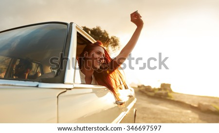 Shot of beautiful young woman enjoying road trip on a summer day. Excited young female raising her hand out of the car. - stock photo