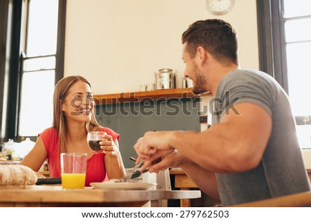 Shot of cheerful young couple having breakfast in kitchen at home. Young woman drinking coffee looking at man smiling while sitting at breakfast table together. - stock photo