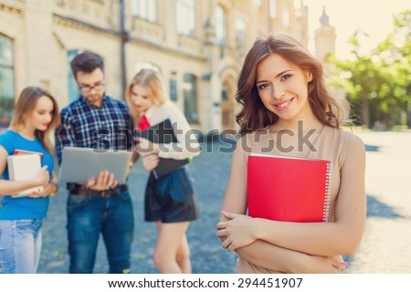 Shot of college students hanging out on campus. Happy classmates - stock photo