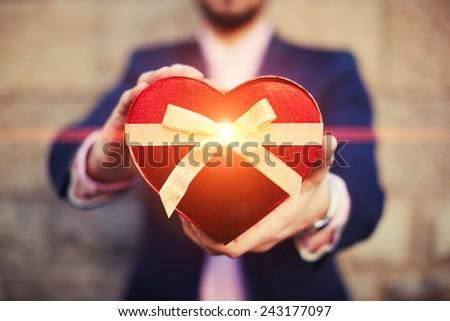 Shot of elegant man giving a Saint Valentine's gift towards the camera - stock photo