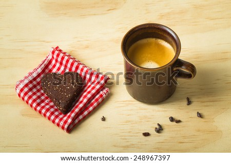 Shot of espresso with healthy dark chocolate, almond, chia seed heart cookie - stock photo