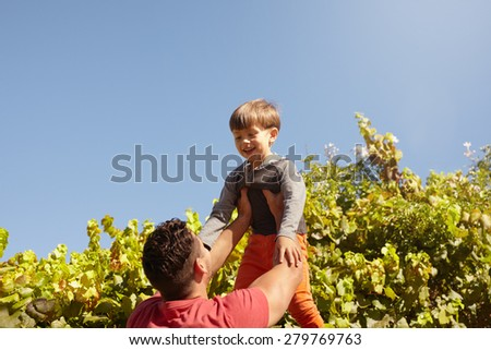 Shot of father lifting his son high in the air. Happy father and son playing outdoors on a sunny day. - stock photo