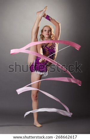Shot of flexible young gymnast dancing with ribbon - stock photo