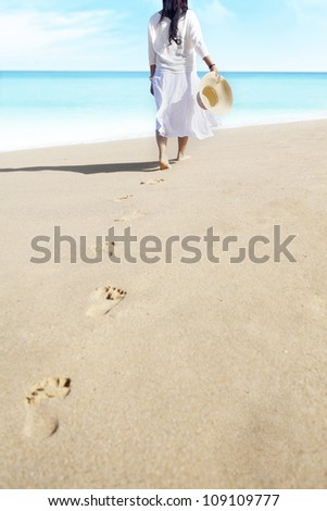 Shot of footprints with woman walks on the tropical beach. shot outdoor - stock photo