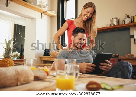 Shot of happy young man and woman using digital tablet in morning. Couple using touchpad in kitchen smiling. - stock photo