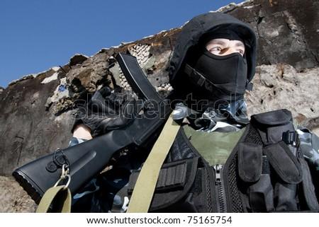 Shot of man in full ammunition holding black automatic gun - stock photo