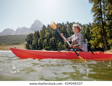 Shot of senior woman kayaking on lake on a summer day. Mature woman paddling a kayak in lake. - stock photo
