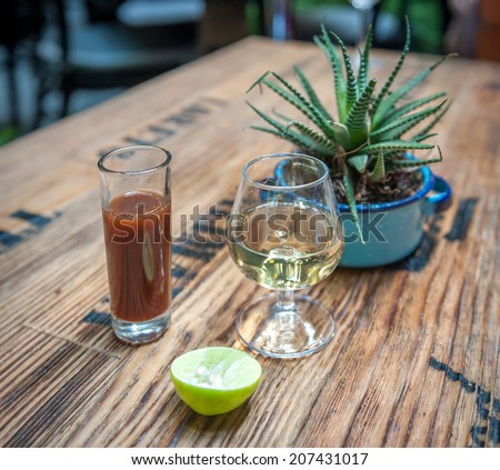 Shot of tequila, sangrita and lime - drink mexican style  - stock photo