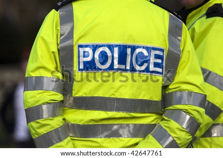 Shot of the back of a police officer's jacket with the word police written across the back - stock photo