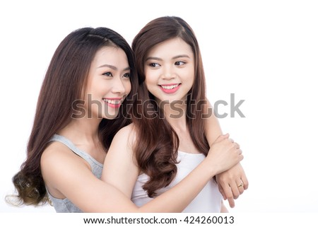 Shot of two attractive young woman smiling hugging isolated on white background. - stock photo