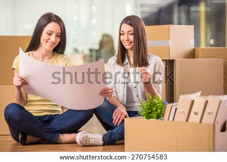 Shot of two businesswomen sitting on th floor and planning out their new office space. - stock photo