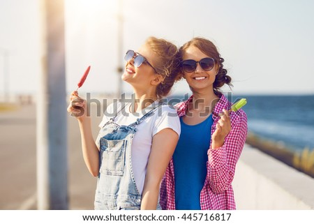 Shot of two young friends enjoying ice lollies on a summer day - stock photo