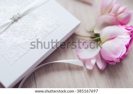 Shot of wedding invitation card and flower. Handmade wedding card - stock photo