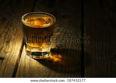 shot of whiskey on old wooden surface - stock photo