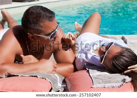 Shot of young couple relaxing at the luxury poolside, at travel spa resort pool. Couple in love, summer luxury vacation in Europe. Travel holidays concept. - stock photo