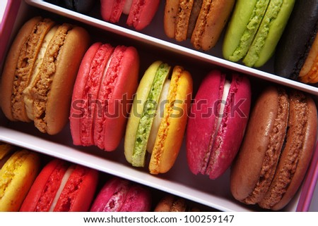 shot taken from above of a box full of macaron or French macaroon, colourful meringue-based almond treats - stock photo
