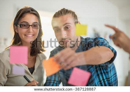 Shot through glass windows. Two colleagues standing in a luminous office. they are watching at some adhesive note on the window.Shot with flare - stock photo