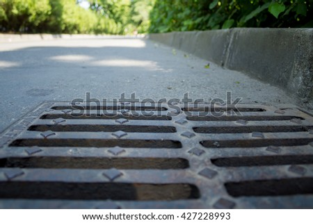 Shot to a sewer at the edge of sidewalk - stock photo