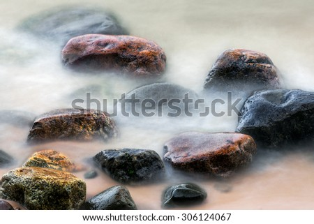 Shot with a long exposure time, colorful stones on a northern Michigan beach are surrounded by the ebb and flow of Lake Superior waves. - stock photo