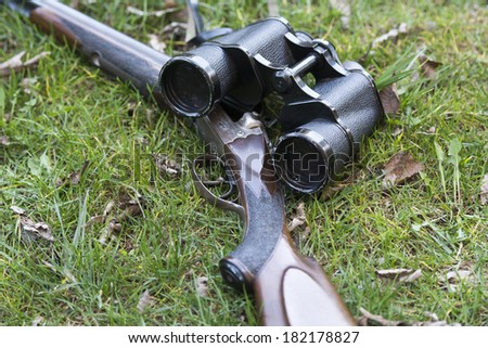 Shotgun and binoculars on grass - stock photo