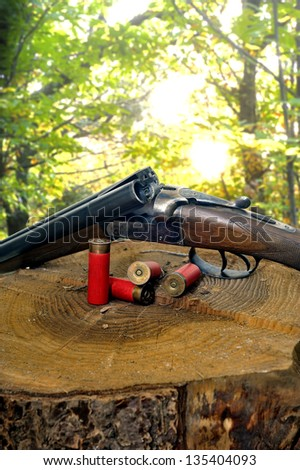 shotgun and its cartridges. Still life representing hunting. - stock photo