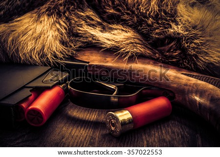 Shotgun lying next to the animal's fur produced and magazine with red cartridges 12 gauge. View close-up, focus on the magazine, image vignetting and the yellow-blue toning - stock photo