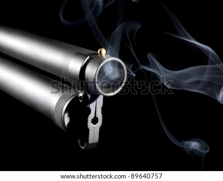 Shotgun muzzle that has smoke coming out with a black background - stock photo