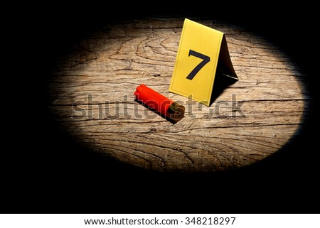 shotgun shell marked as evidence in a spot light - stock photo