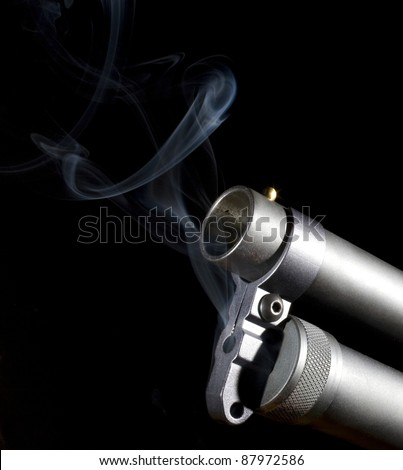 Shotgun that has smoke rising from around the end of its muzzle - stock photo