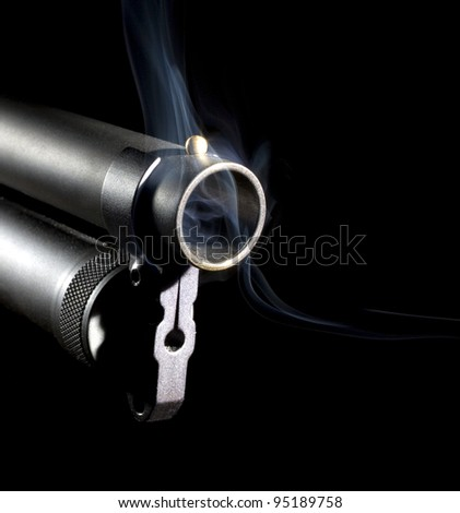 Shotgun with a brass bead front sight that is smoking - stock photo