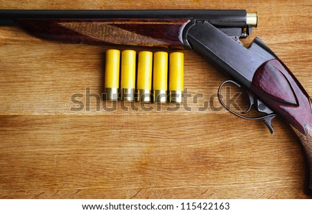 shotgun with shells on wooden background - stock photo