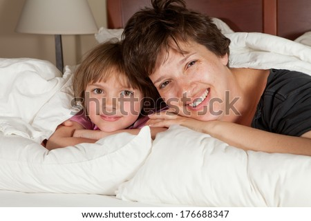 Shots of a mother  daughters waking up in bed with white linens part of a series - stock photo