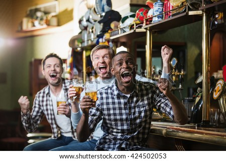 Shouting fans with a beer at a bar - stock photo